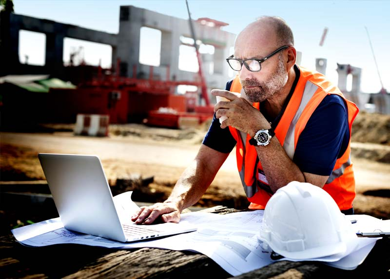 Worker on site using laptop with hard hat and plans