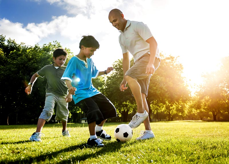Man playing soccer with two boys