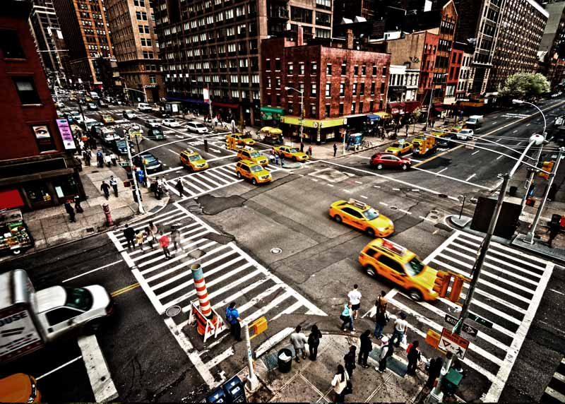 Taxis crossing through a busy city intersection