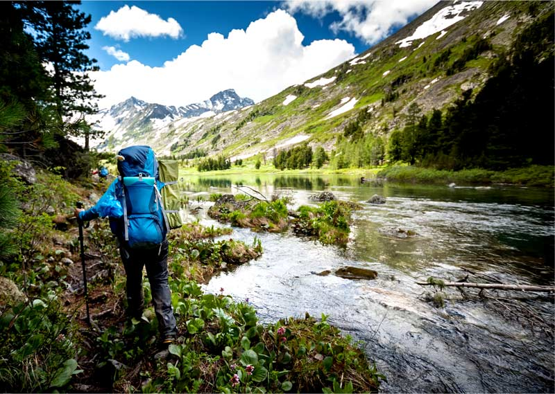 Person hiking near a river towards mountains